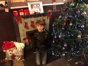 Nathan in a festive scene with Christmas tree