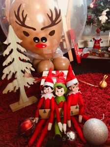 3 elves with festive items and Rudolph balloon